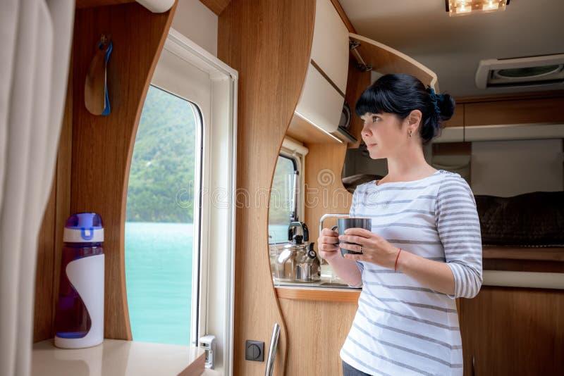 Mulher no interior de um motorhome do campista rv com uma xícara de café que olha a natureza fotografia de stock royalty free