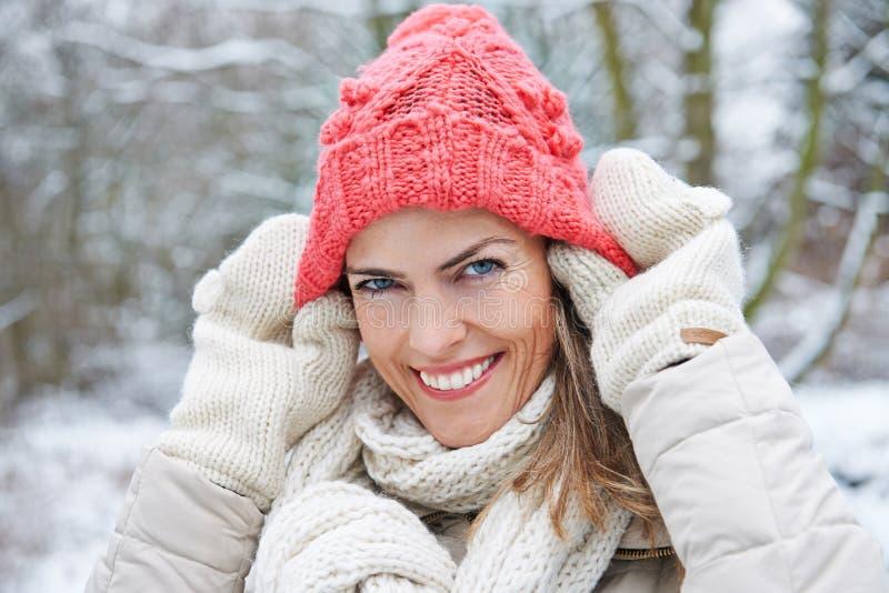 Mulher no inverno que põe o tampão de lãs sobre fotografia de stock