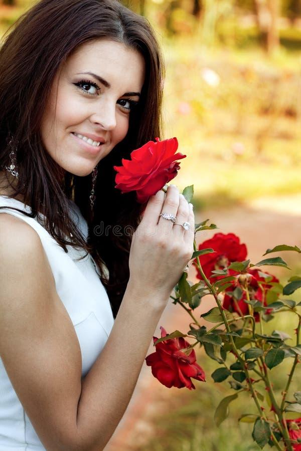 Mulher no jardim de flor que cheira rosas vermelhas foto de stock
