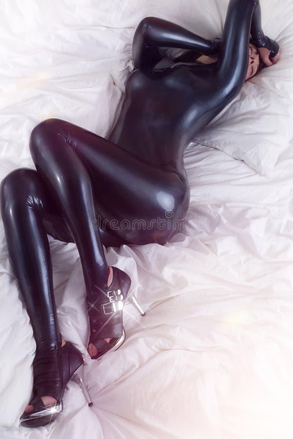 Mulher no látex na cama foto de stock royalty free