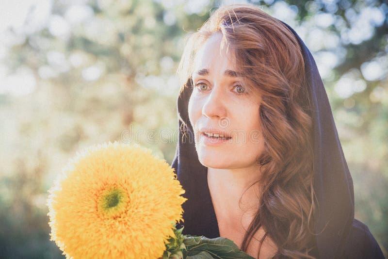A mulher no lenço no parque, rasgos em seus olhos, sorrindo e guardando perto da cara de um girassol emoções imagem de stock