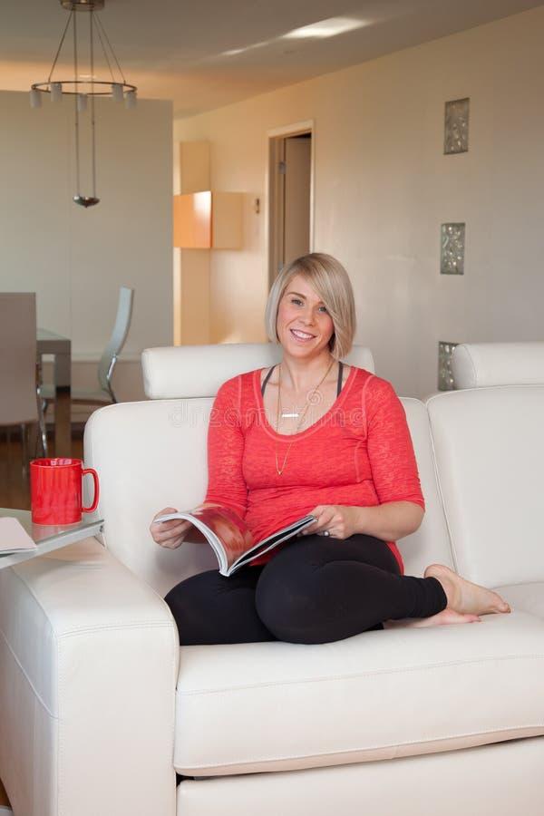 Mulher no livro de leitura do sofá fotografia de stock royalty free