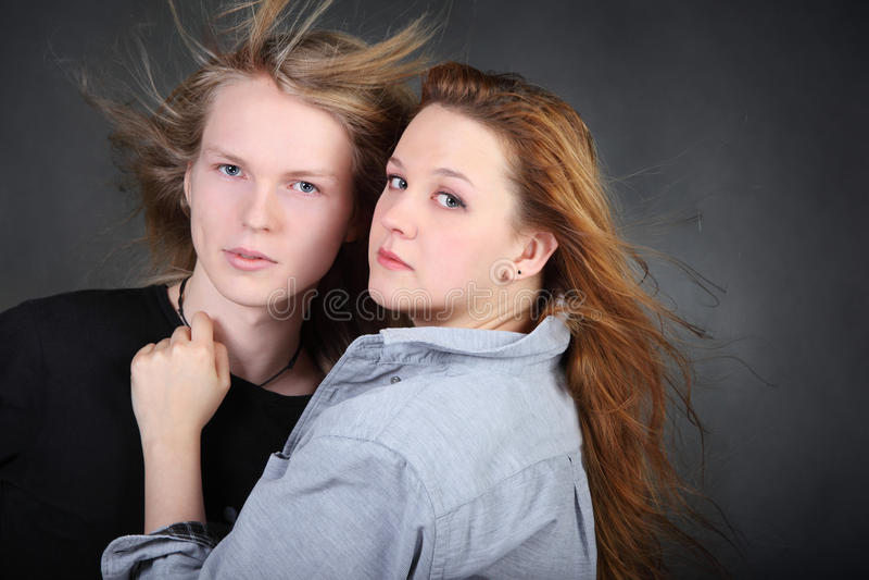 Mulher no menino longo do cabelo do hug da camisa no estúdio da foto fotografia de stock