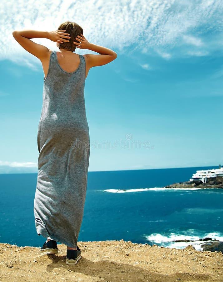 A mulher no moderno ocasional veste a posição no penhasco da montanha fotografia de stock royalty free
