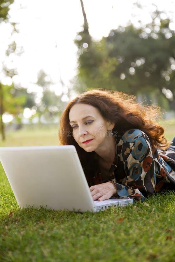 Mulher no parque com portátil fotos de stock royalty free