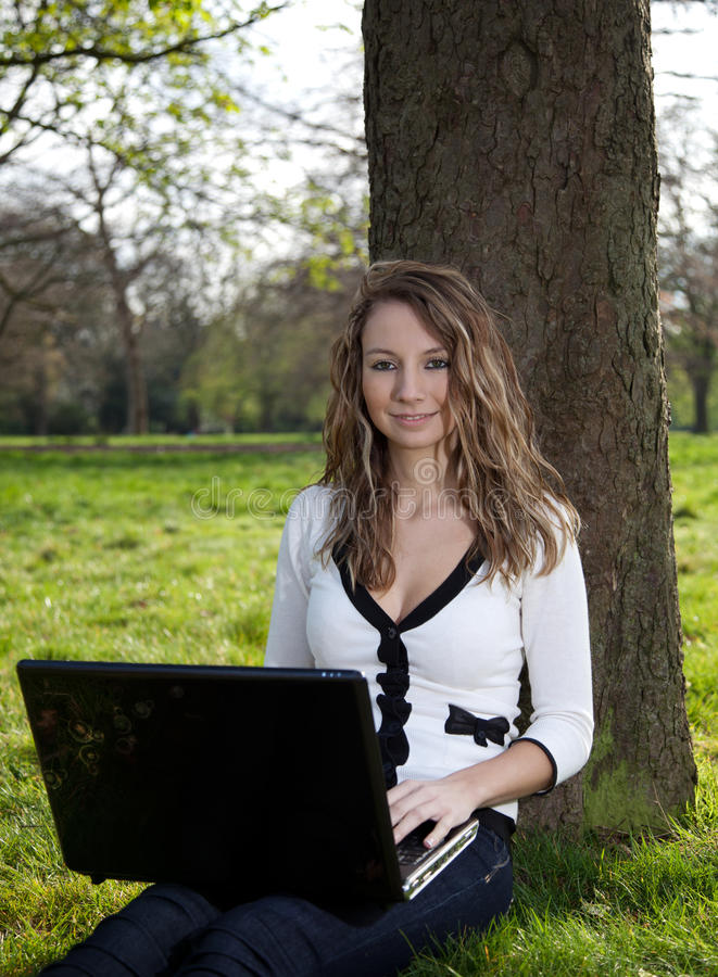 Mulher no parque com portátil imagem de stock royalty free