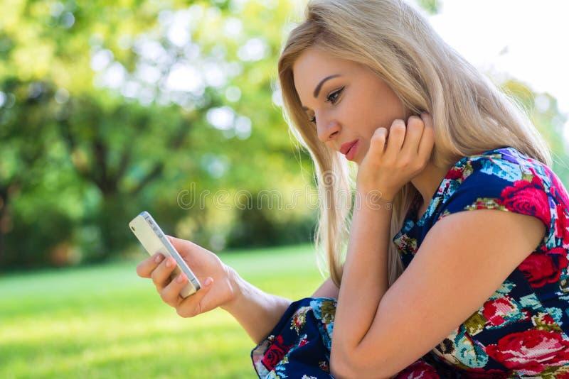 Mulher no parque com telefone esperto imagem de stock royalty free