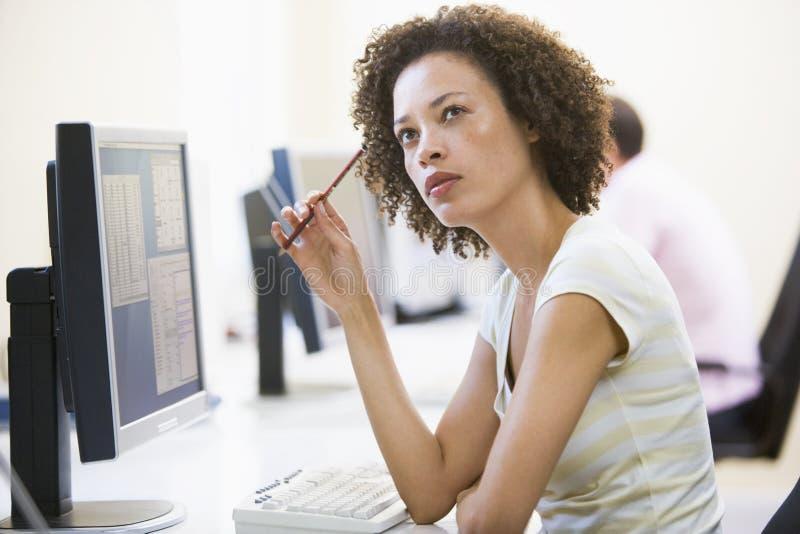 Mulher no pensamento do quarto de computador imagem de stock royalty free