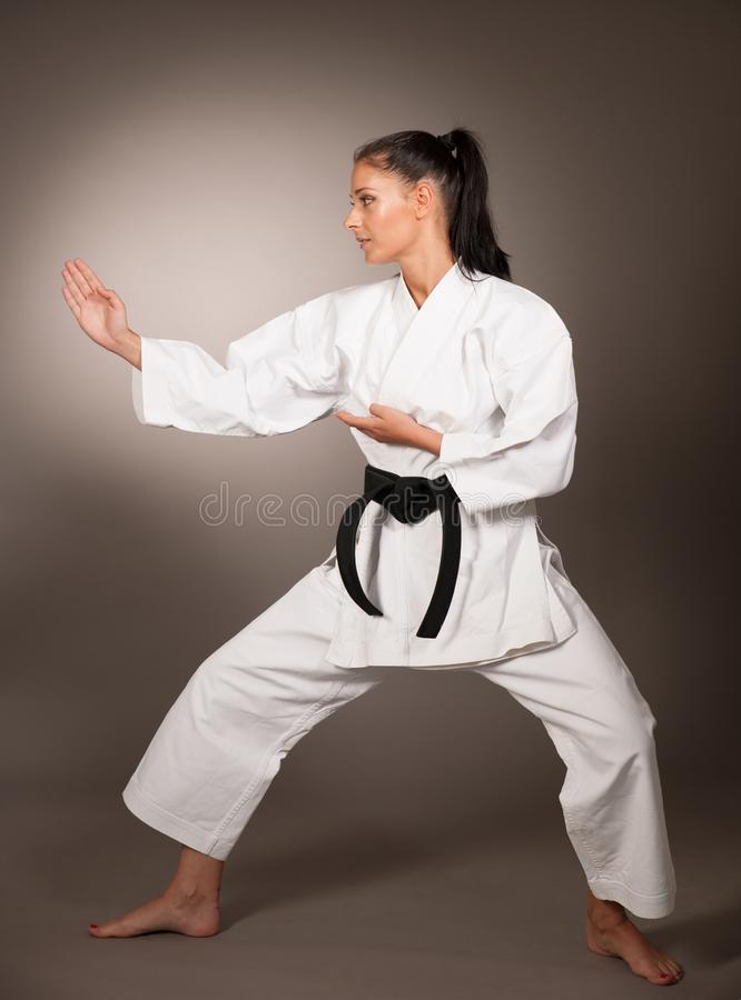 Mulher no perfurador branco do quimono duramente no ar - um karaté marcial fotografia de stock