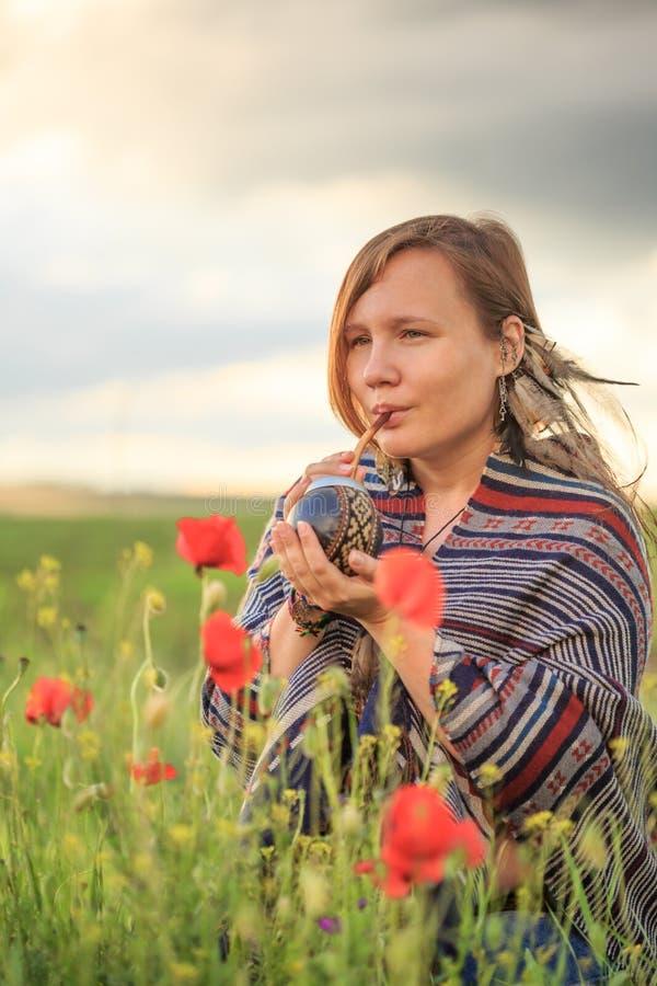 Mulher no poncho com o cabaceiro no campo de flor imagens de stock royalty free