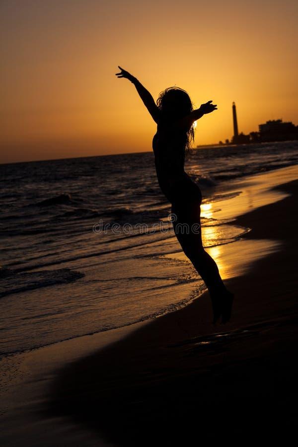 mulher no por do sol da praia imagem de stock royalty free