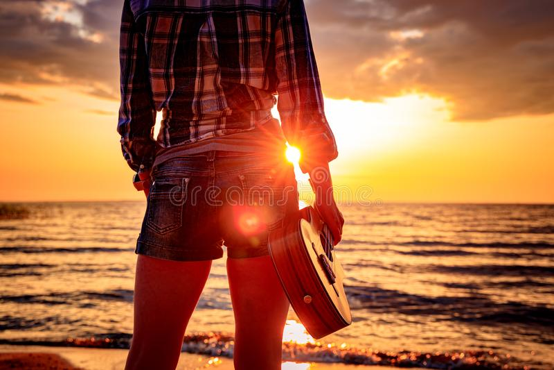 Mulher no por do sol que guarda uma uquelele fotos de stock royalty free