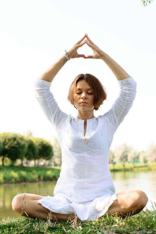 Mulher no pose da meditação As mãos são lugares acima da cabeça foto de stock