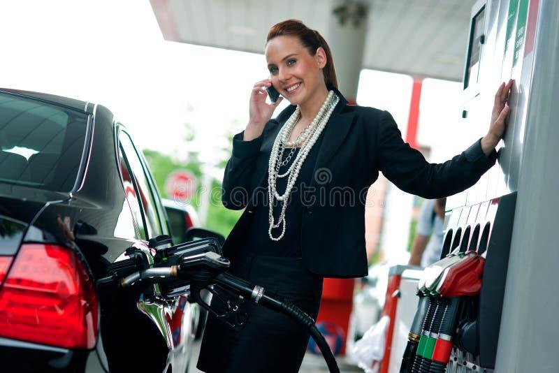 Mulher no posto de gasolina que fala ao telefone móvel imagem de stock royalty free