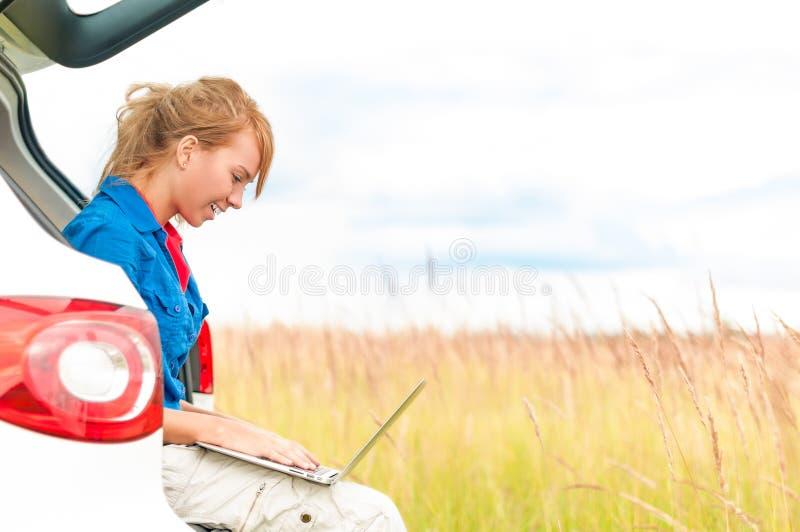 Mulher no prado perto do carro que trabalha no portátil. fotografia de stock