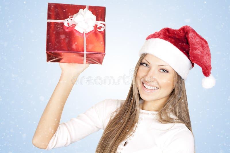 Mulher no presente do Natal da terra arrendada do chapéu de Santa imagem de stock