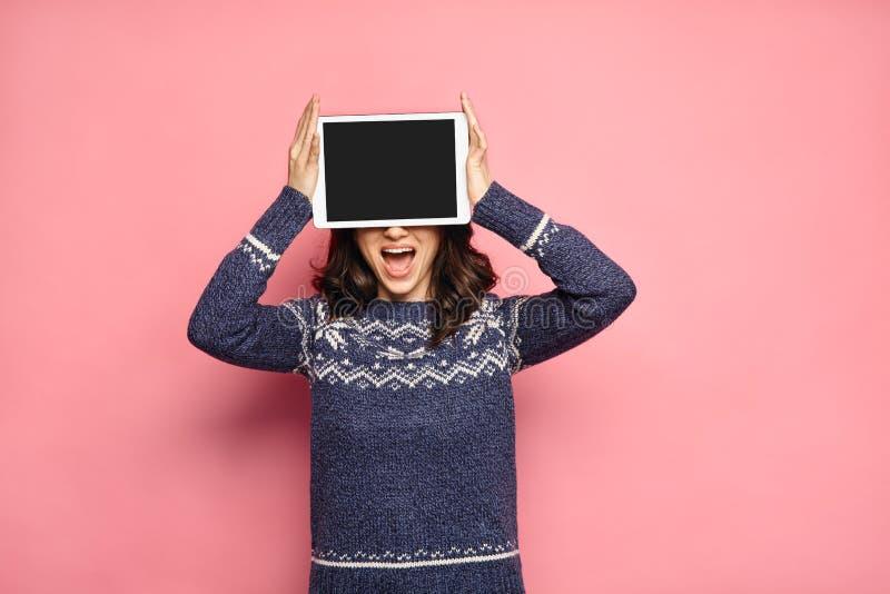 Mulher no pulôver do inverno que mostra a tela de tablet pc vazia fotografia de stock royalty free
