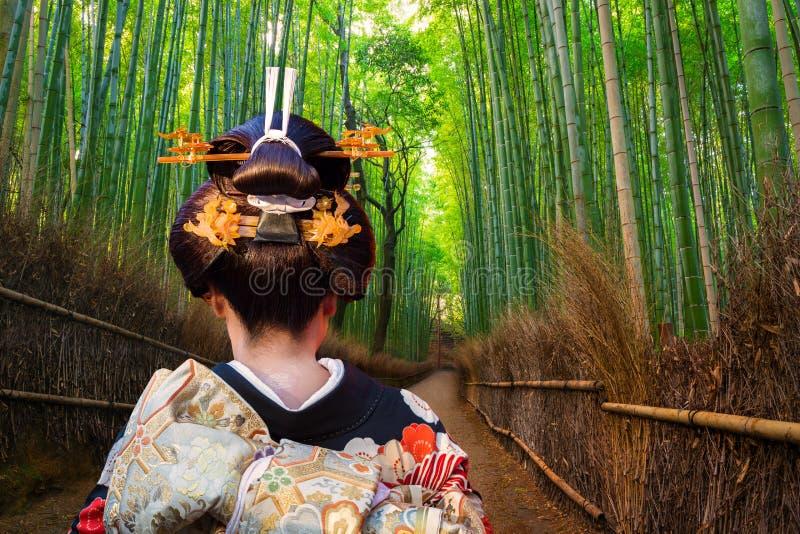 Mulher no quimono tradicional que anda na floresta de bambu de Arashiyama, Japão foto de stock royalty free