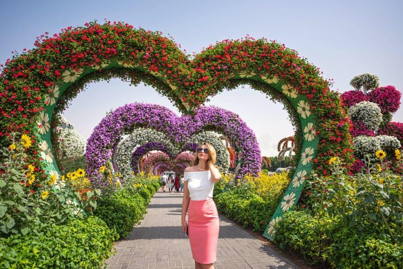 Mulher no retrato do jardim de Dubai Fundos bonitos das flores do dia ensolarado fotografia de stock