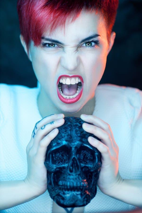 Mulher no revestimento branco com cabeça preta falsificada do crânio fotografia de stock royalty free