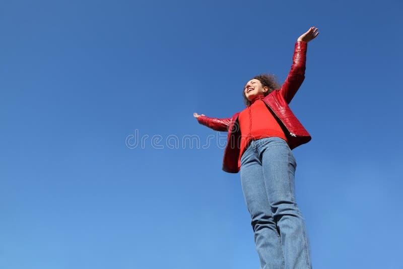 A mulher no revestimento e em calças de brim vermelhos levanta sua mão imagem de stock