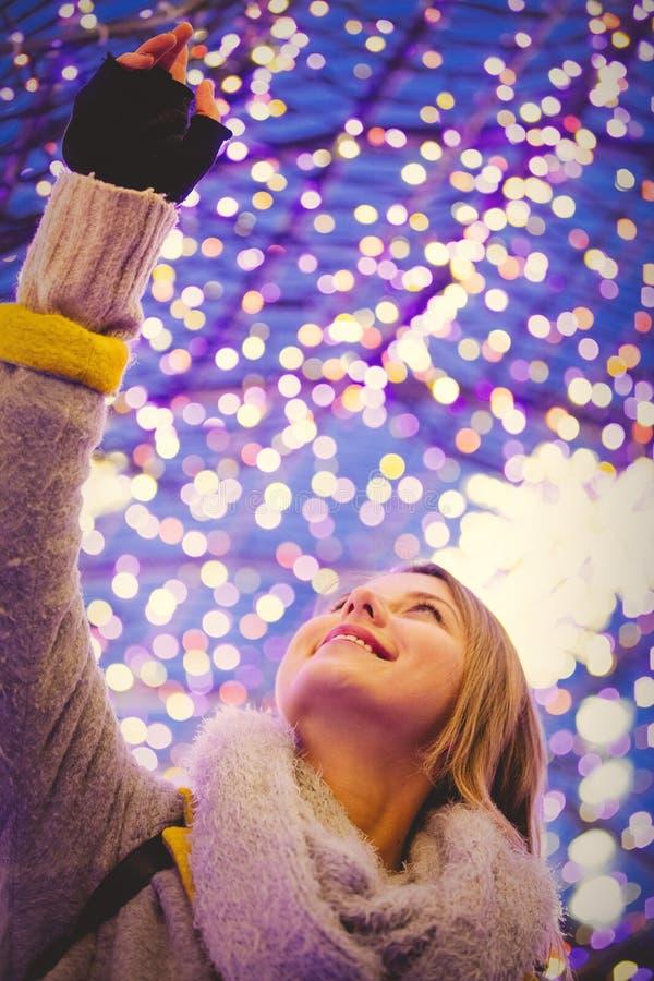 Mulher no revestimento e no lenço com luz do tempo do Natal imagem de stock