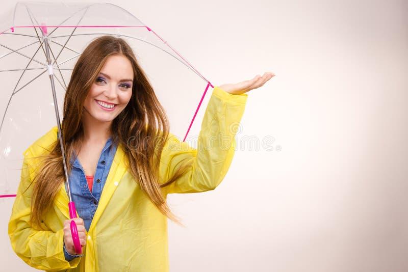 Mulher no revestimento impermeável com guarda-chuva forecasting fotografia de stock