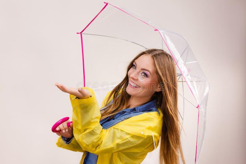 Mulher no revestimento impermeável com guarda-chuva forecasting imagens de stock