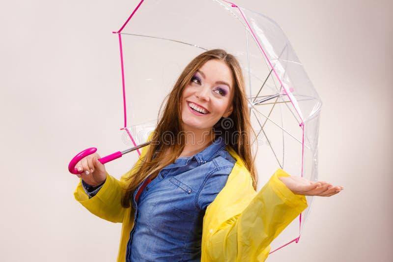 Mulher no revestimento impermeável com guarda-chuva forecasting fotos de stock