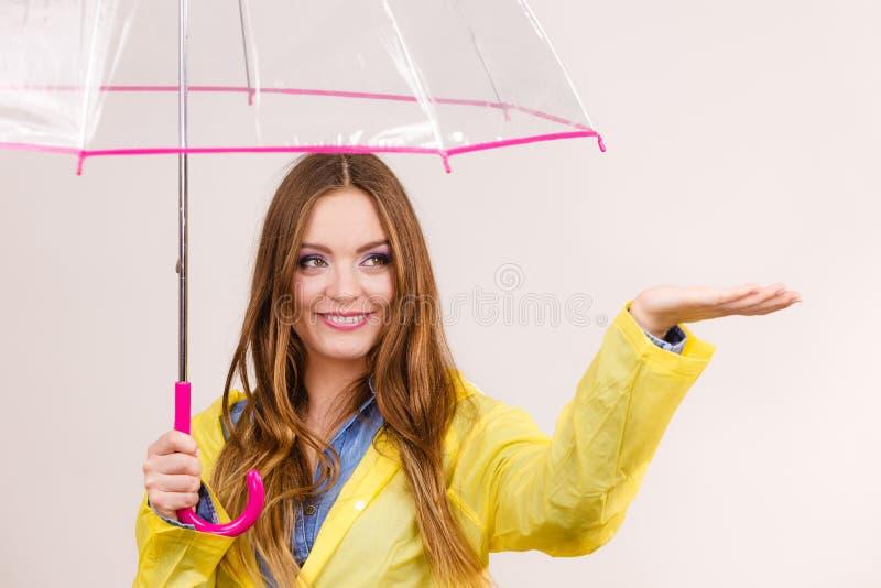 Mulher no revestimento impermeável com guarda-chuva forecasting imagem de stock royalty free