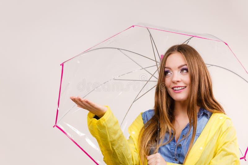 Mulher no revestimento impermeável com guarda-chuva forecasting fotos de stock royalty free