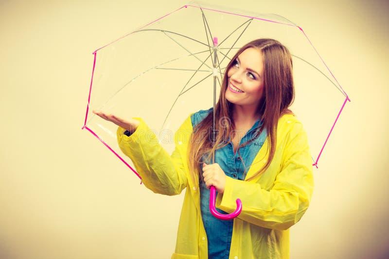 Mulher no revestimento impermeável com guarda-chuva forecasting fotografia de stock royalty free