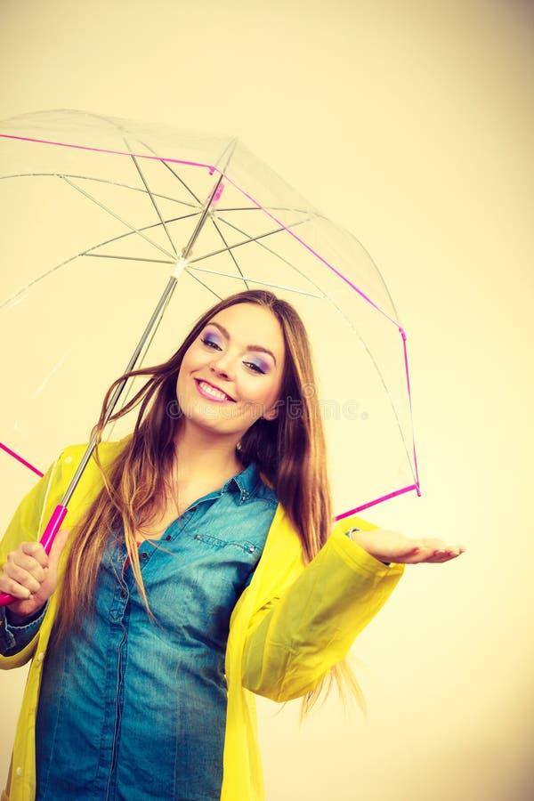 Mulher no revestimento impermeável com guarda-chuva forecasting foto de stock