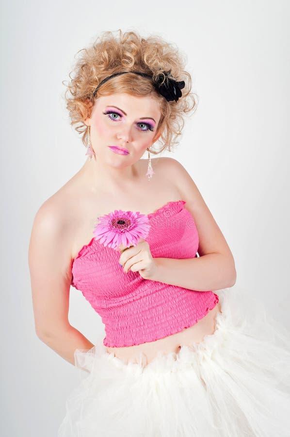 A mulher no rosa demonstra uma boneca fotos de stock