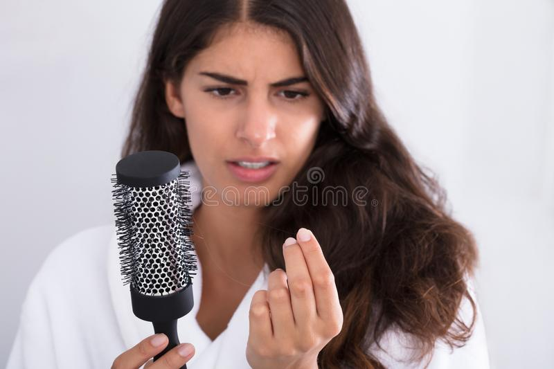 Mulher no roupão que guarda o pente que olha a queda de cabelo fotografia de stock royalty free