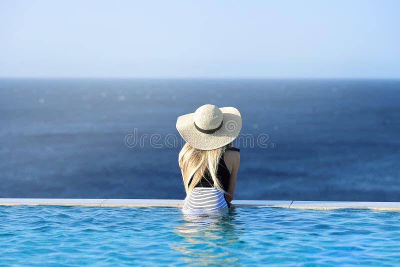 Mulher no roupa de banho na piscina da infinidade com opinião do mar no recurso luxuoso Parte traseira fêmea no roupa de banho co fotos de stock royalty free