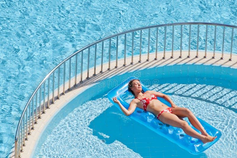 A mulher no roupa de banho toma sol o encontro no colchão inflável imagem de stock