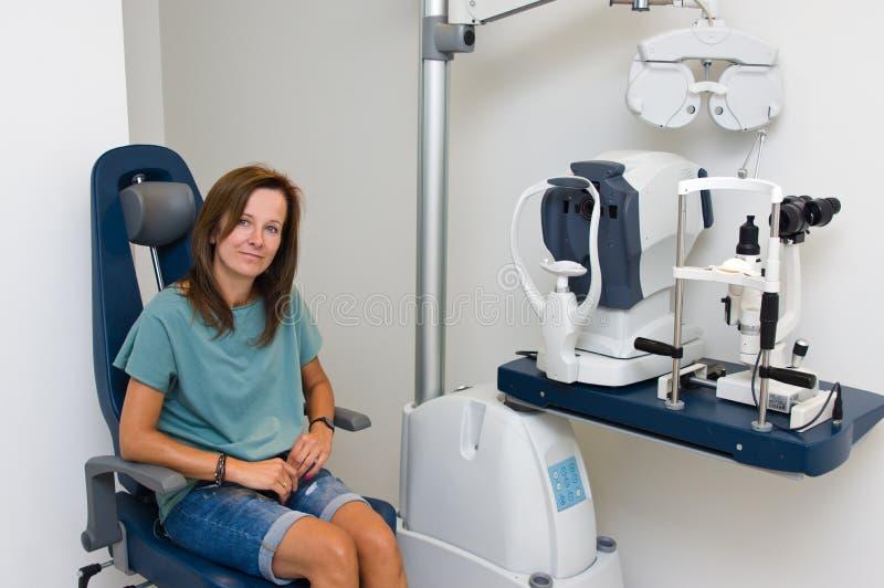 Mulher no salão de beleza do optometrista que verifica sua visão imagem de stock