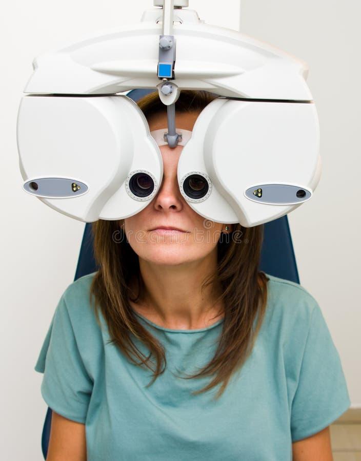 Mulher no salão de beleza do optometrista que verifica sua visão fotografia de stock