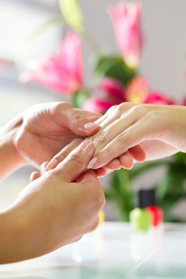 Mulher no salão de beleza do prego que recebe a massagem da mão fotografia de stock