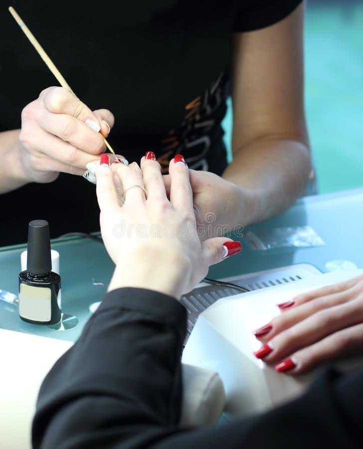 Mulher no salão de beleza do prego que recebe o tratamento de mãos pelo esteticista Mulher que obtém o tratamento de mãos no salã imagem de stock