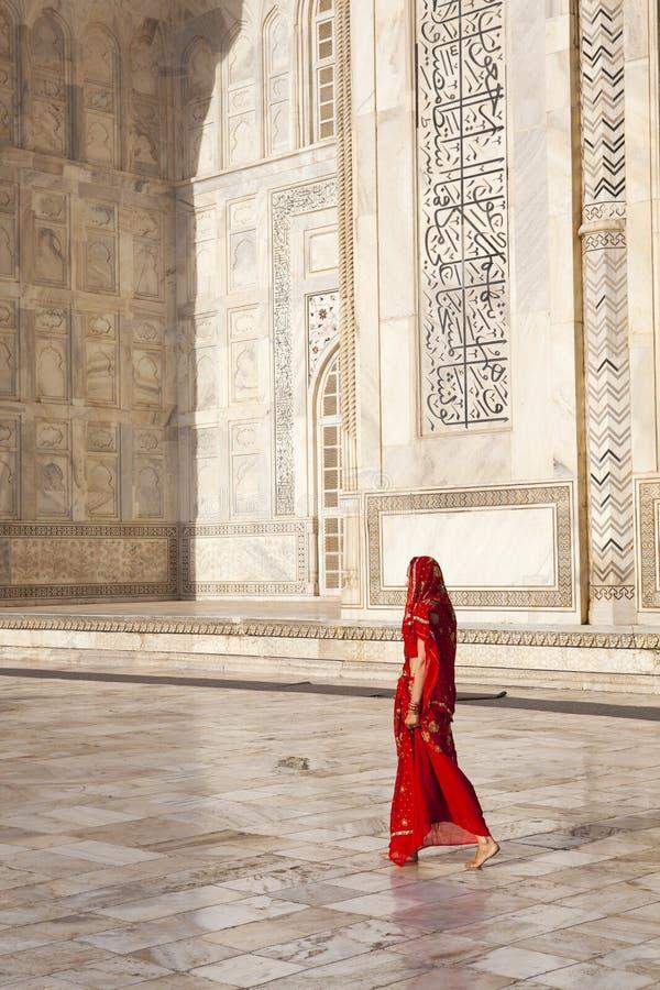 Mulher no saree vermelho em Taj Mahal. fotografia de stock royalty free