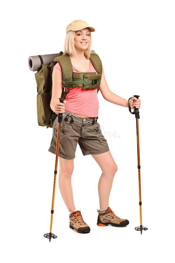 Mulher no sportswear com trouxa e pólos da caminhada foto de stock