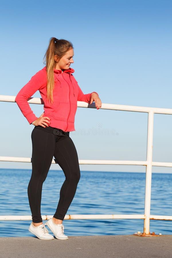 Mulher no sportswear que está no dique pelo mar fotografia de stock