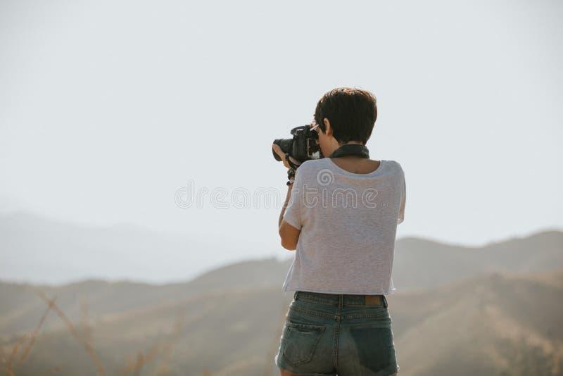 Mulher no t-shirt que toma uma foto com uma câmera do dslr na natureza com luz do dia imagens de stock royalty free