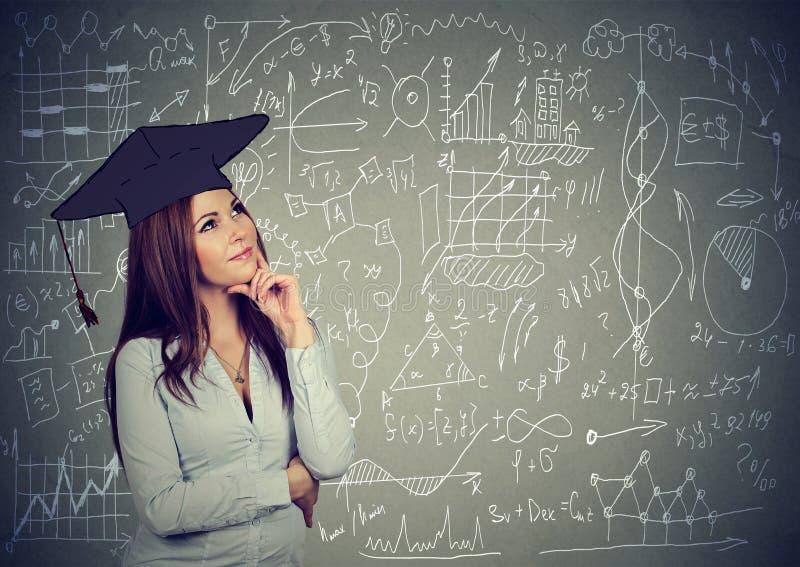 Mulher no tampão da graduação que pensa sobre a educação, equilíbrio da vida do trabalho que está pelo fundo do quadro-negro dos  imagem de stock royalty free