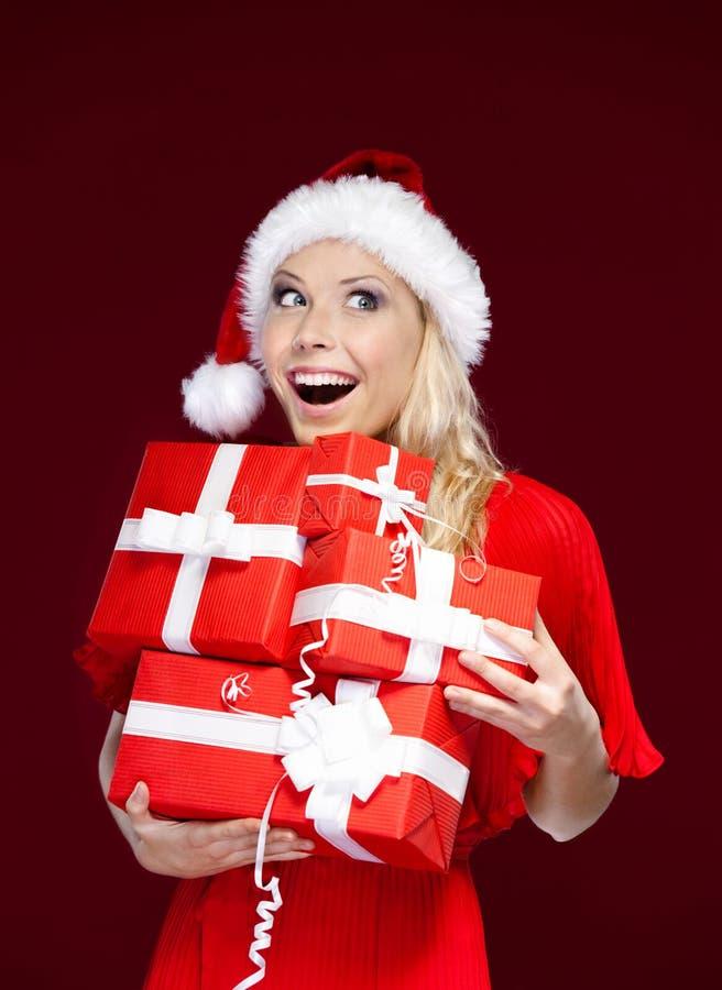 A mulher no tampão do Natal prende um jogo dos presentes fotos de stock royalty free