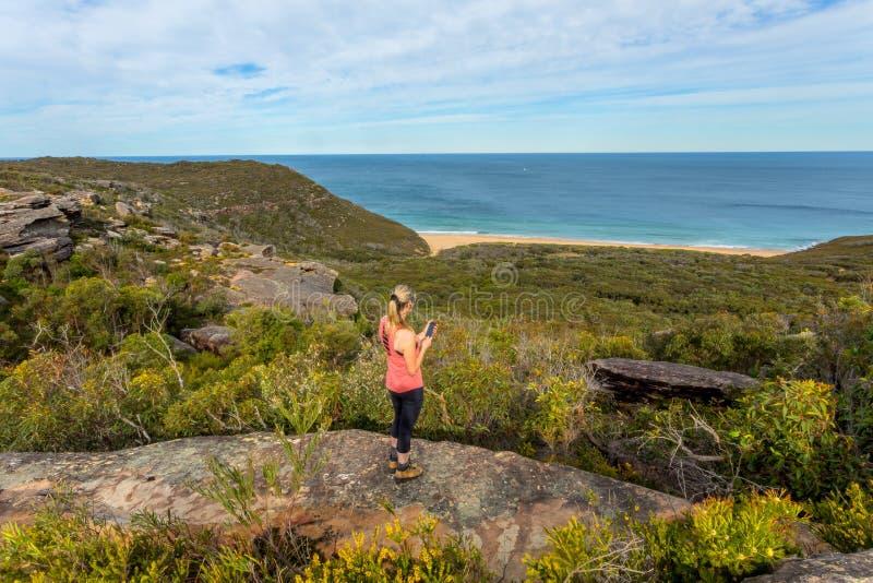 Mulher no telefone celular da terra arrendada do clifftop, vistas à praia do oceano imagens de stock