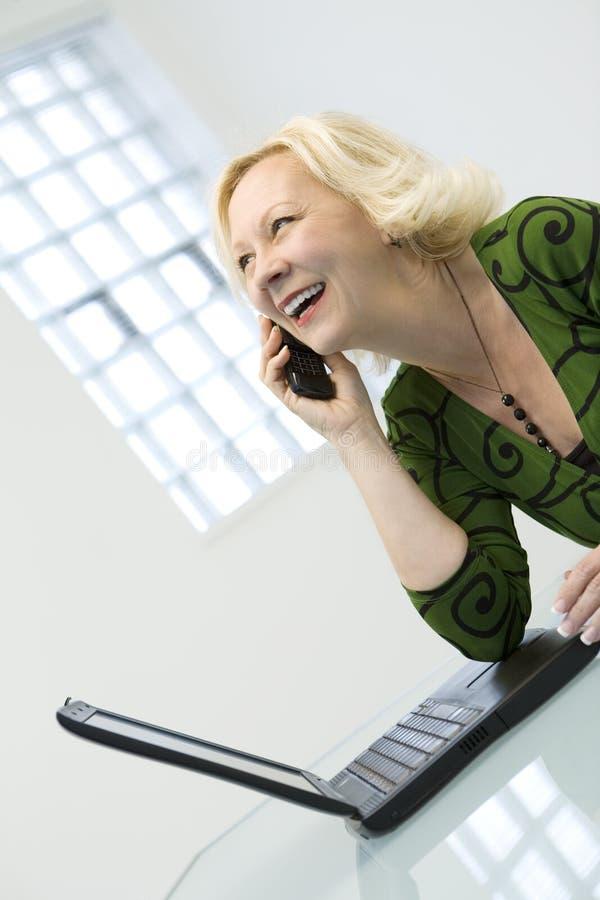 Mulher no telefone com portátil fotos de stock royalty free