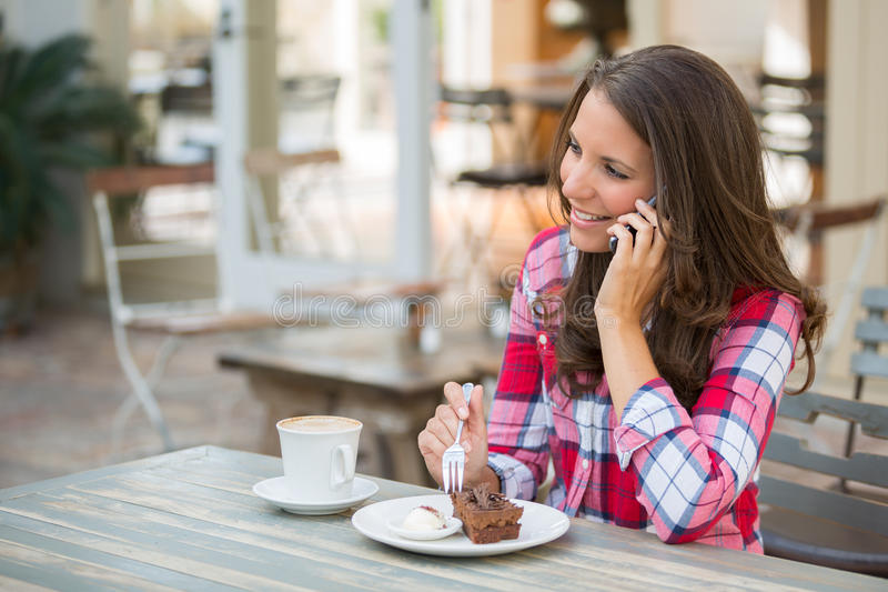 Mulher no telefone que come o bolo fotos de stock